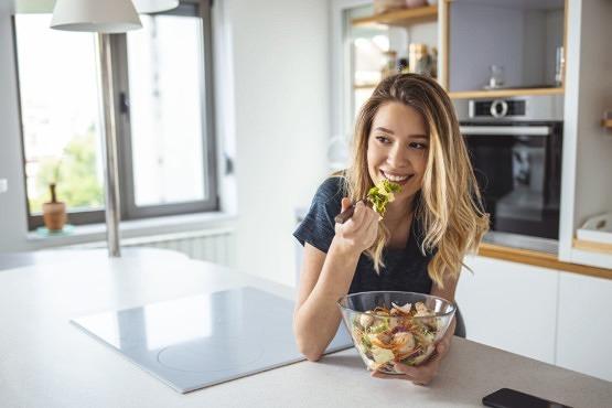 Mujer comiendo alimentos que reducen el acné y el maskné