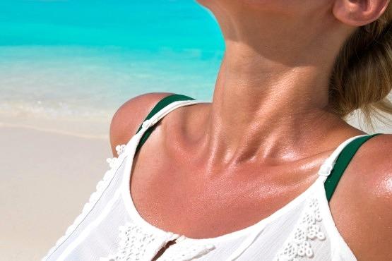 Mujer tomando el sol con fotoprotección para evitar el daño solar